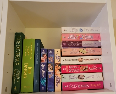 Square cubby of books. There's a horizontal stack made up largely of Judith McNaught and Kathleen Woodiwiss books, with a Nora Roberts at the bottom. The rest of the shelf is horizontal books, including several hardcovers by Jude Deveraux and paperbacks by Laura Kinsale, Stephanie Laurens, and Loretta Chase