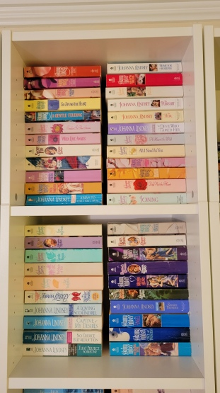 Two square cubbies stuffed with Johanna Lindsey books organized in two columns per cubby